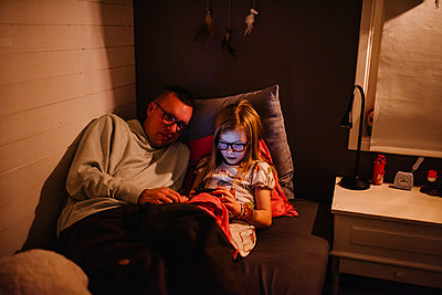 Father with daughter sitting on bed and looking at cell phone - p312m2249299 by Anna Johnsson
