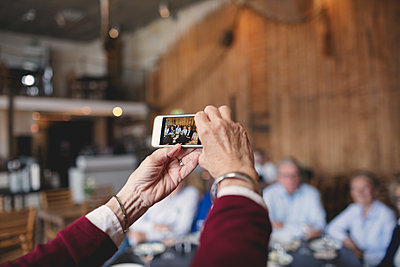 Cropped image of senior woman photographing friends with smart phone at restaurant - p426m1506300 by Maskot