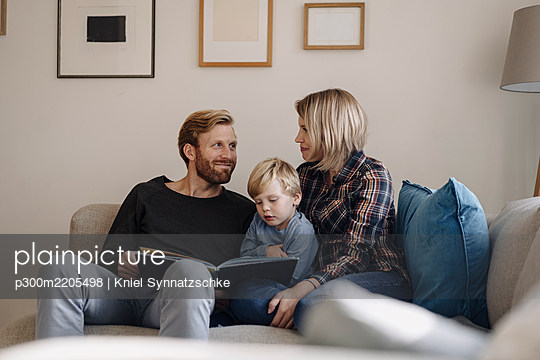 Family looking at book on couch at home - p300m2205498 by Kniel Synnatzschke