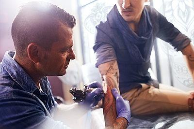 Tattoo artist tattooing manÕs forearm - p1023m1121375f by Trevor Adeline