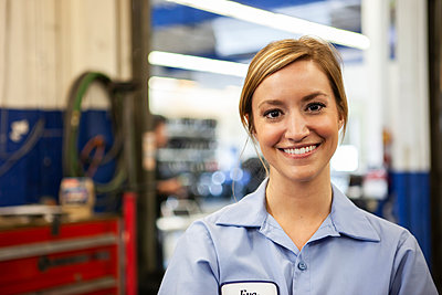 Portrait of young female Caucasian mechanic in auto repair shop - p1100m2249014 by Mint Images