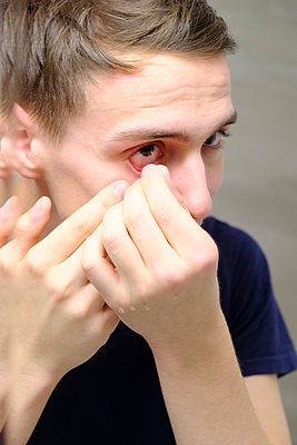 Junger Mann entfernt seine Kontaktlinsen - p1105m2086512 von Virginie Plauchut