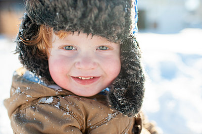 Up close of cute toddler in winter clothes and hat smiling in the snow - p1166m2136745 by Cavan Images