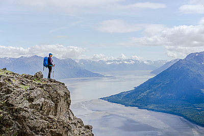 Female hiker at Hope Point in Chugach National Forest Alaska overlooking Turnagain Arm - p343m1446747 by The Open Road Images