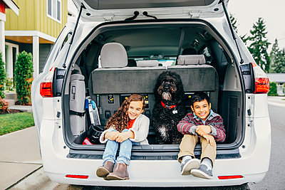 Mixed race children sitting with dog in car hatch - p555m1305906 by Inti St Clair