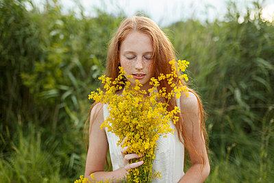 Caucasian girl smelling wildflowers - p555m1521402 by Vyacheslav Chistyakov
