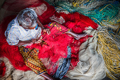 Fisherman mending net at Kappil Beach, Varkala, Kerala, India - p871m2032213 by Photo Escapes