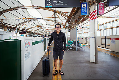 Smiling man with wheeled suitcase standing on the platform of a subway station, Tokyo commuter.  - p1100m1531112 by Mint Images