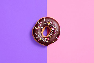 Overhead view of chocolate donut on colored background - p1166m2025494 by Cavan Images