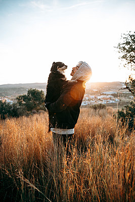 Young man with his dog during sunrise, Montroy, Spain - p300m2170429 by REBELARTE