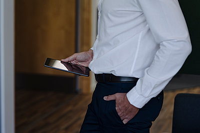 Businessman with hands in pockets holding digital tablet while standing at office - p300m2221039 by Joseffson