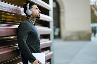 Hipster man with headphones holding digital tablet while standing against metal wall - p300m2252623 by Jose Carlos Ichiro