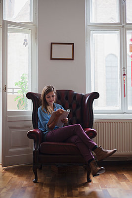 Beautiful young female university student sitting on armchair while reading book at home - p301m1498682 by Larry Washburn