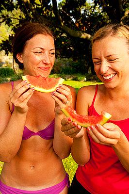 Happy female friends eating watermelon at park - p426m747495f by Erik Leonsson