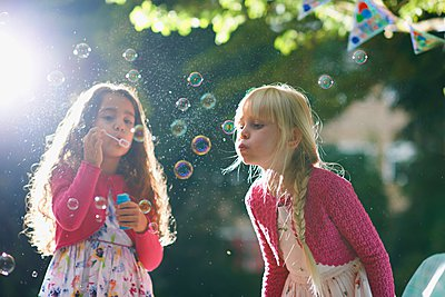 Two girls blowing bubbles in sunlit garden - p429m1062297f by Peter Muller