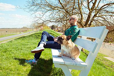 Mann und Hund entspannen auf Bank - p432m1225878 von mia takahara