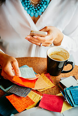 Businesswoman examining fabric samples in cafe - p555m1408576 by Inti St Clair