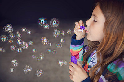 Caucasian girl blowing bubbles - p555m1409671 by Shestock