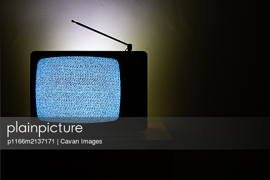 Old vintage television isolated on dark background with no signal and grainy noise