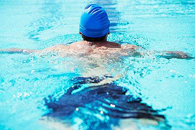 Swimmer floating in pool - p1023m923688f by Paul Bradbury