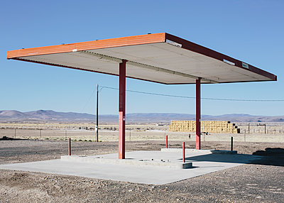 Abandoned rural gas station, hay bales in the distance,  - p1100m1220558 by Mint Images
