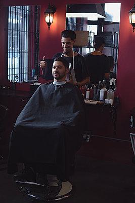 Man looking his new hair cut in the mirror - p1315m1579061 by Wavebreak