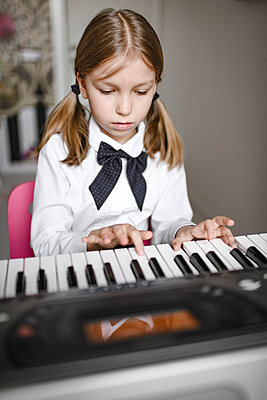 Portrait of focused a girl playing synthesizer - p300m2102886 by Ekaterina Yakunina