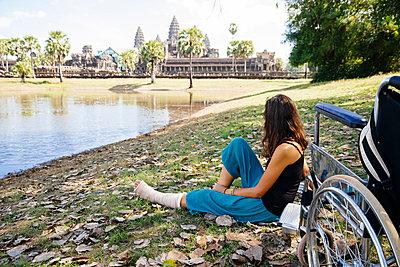 Cambodia, Siem Reap, Angkor, woman with broken leg and wheelchair looking at Angkor Wat - p300m873662 by Martin Benik