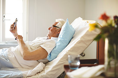 Senior man taking selfie with smart phone on bed in hospital ward - p426m1494039 by Maskot