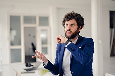 Young businessman gesturing in office - p586m1562023 by Kniel Synnatzschke