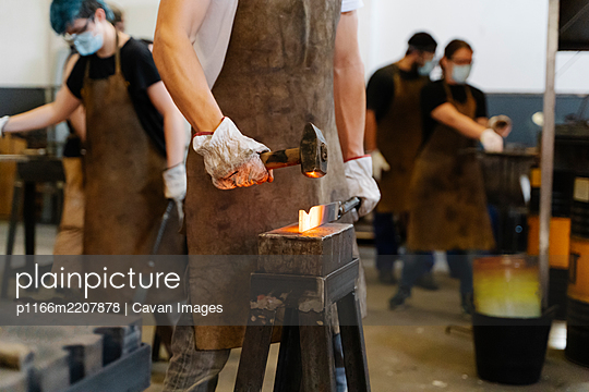 Crop blacksmiths hitting hot metal detail with hammer while forging - p1166m2207878 by Cavan Images