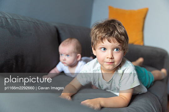 Two boys lying on the sofa - p1166m2292660 by Cavan Images