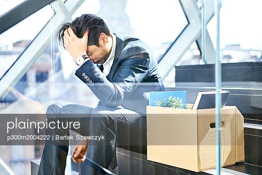 Depressed businessman sitting on stairs with belongings in cardboard box beside him - p300m2004222 von Bartek Szewczyk