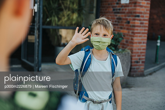 Little boy wearing protective face mask waving his brother outside school building - p300m2226879 by Mareen Fischinger