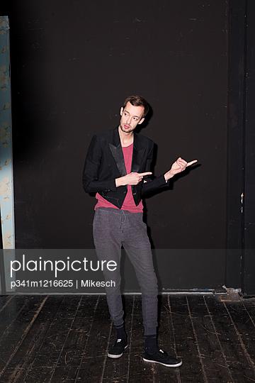 Junger Mann gestikuliert, Porträt - p341m1216625 von Mikesch
