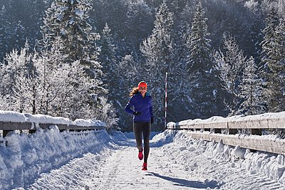 Germany, Bavaria, Isar valley, Vorderriss, woman jogging in winter - p300m1356004 by Michael Reusse (alt)