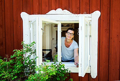 Mature woman looking out window - p352m2119854 by Lena Katarina Johansson