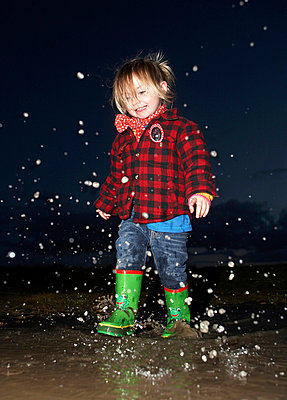 Girl splashing in puddle at night - p429m711799f by Nick Stevens