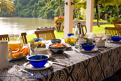 Private home in Parati Brazil. Back terrace, overlooking the sea, with the table set for breakfast. - p855m664417 by Amanda Holmes