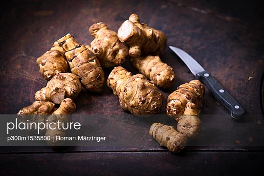Jerusalem artichokes and kitchen knife on rusty ground - p300m1535890 by Roman Märzinger