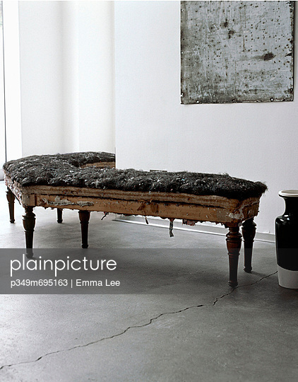 A vintage bench seat in need of re-upholstering - p349m695163 by Emma Lee