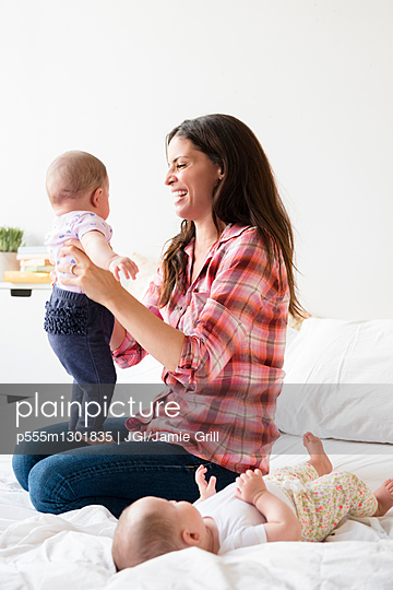 Caucasian mother playing on bed with twin baby daughters - p555m1301835 by JGI/Jamie Grill