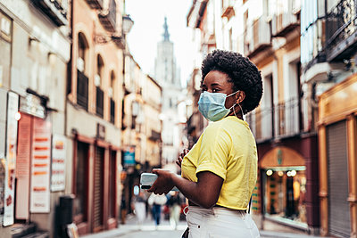 Portrait of black girl with face mask, afro hair and hoop earrings walking down a central street of the old city. - p1166m2269562 by Cavan Images