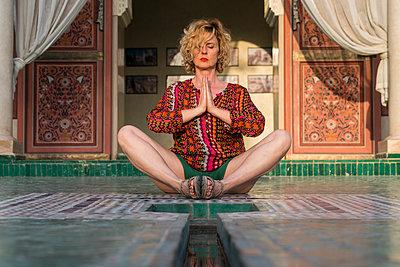 Morocco, Marrakesh, tourist sitting on the floor doing yoga - p300m1449774 by Kike Arnaiz