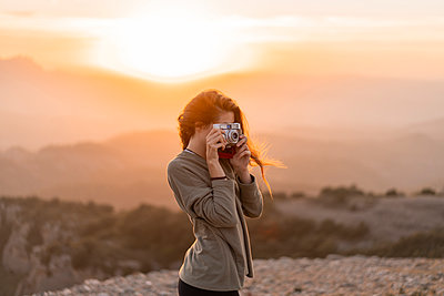 Spain, Barcelona, Natural Park of Sant Llorenc, woman taking a picture with vintage camera at sunset - p300m2058578 by VITTA GALLERY