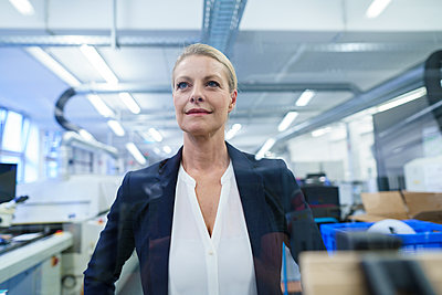 Confident blond businesswoman standing while looking away in illuminated factory - p300m2221616 by Robijn Page