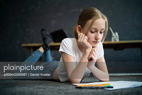 Girl lying on carpet and learning at home - p300m2206587 by Daniel Koebe