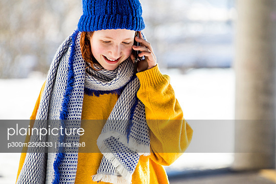 Smiling cute girl in warm clothing talking on mobile phone - p300m2266333 by Irina Heß