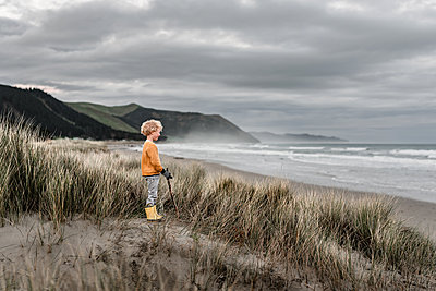 Blond curly haired boy watching ocean on cloudy day in New Zealand - p1166m2207974 by Cavan Images