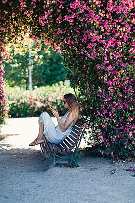 Woman with cell phone sitting on bench in park under pink blossoms - p300m2024193 by Javier Pardina